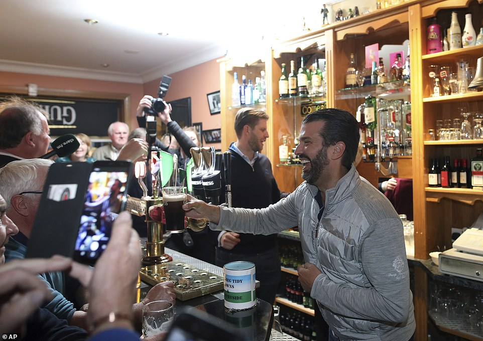 A smiling Don Jr reaches across the bar with a pint of Guinness as his brother Eric scans the back bar for a punter's tipple of choice
